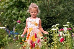 Ленка на цветочной клумбе перед домом.