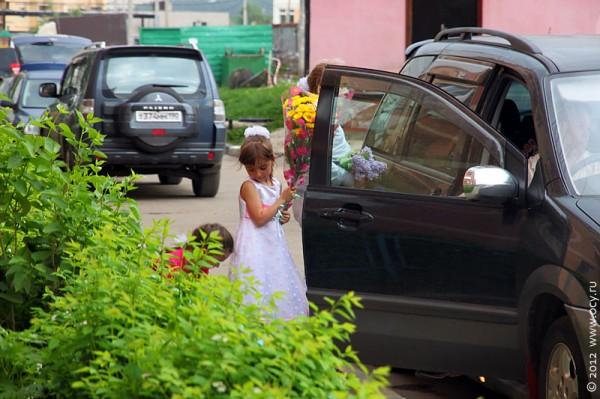 Милана садится в машину.