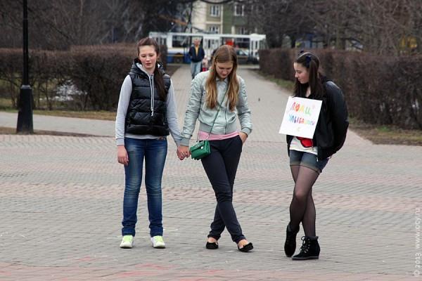 Девушки с плакатом, призывающим улыбаться.